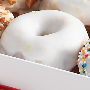 Blueberry mini donut topped with white lemon glaze in a box