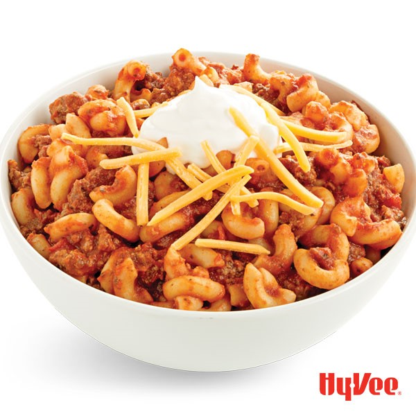 Bowl of chili macaroni and cheese, topped with sour cream and shredded cheese
