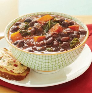 Bowl of black bean soup with sweet potatoes and kale