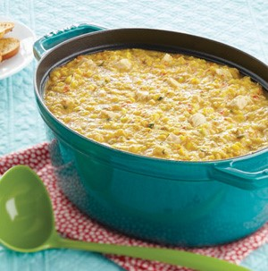 Teal Dutch oven filled with corn chowder next to a green ladle on a red napkin