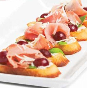 Toasted sliced bread topped with grapes, deli ham, celery, and Swiss cheese