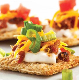 Cracker topped with mayo, bacon, cheese, green onions and tomato