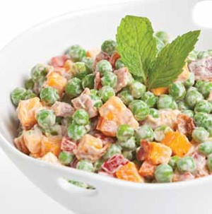 White bowl of cheddar cheese pea salad