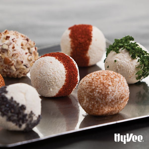 Round cheese balls with various fruit and nut toppings on a metal plate