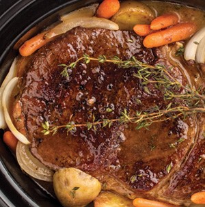 Pot roast with onions, carrots, potatoes and thyme in slow cooker