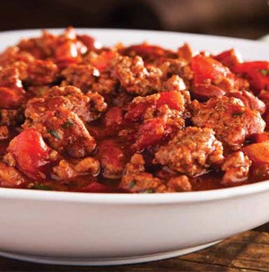 White bowl filled with cooked ground meat and diced tomatoes in a tomato sauce