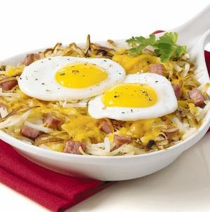 Hashbrowns topped with diced ham, melted cheese, and two fried eggs