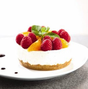 White plate topped with circular tart with graham cracker crust, cream cheese filling and topped with orange segments, whole raspberries and fresh mint