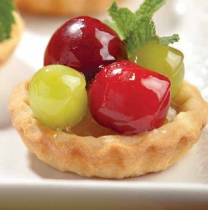Pie crust topped with glazed fresh grapes and fresh mint leaves