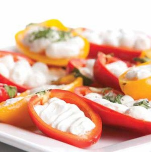 Halved mini bell peppers filled with sour cream and garnished with fresh herbs