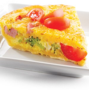 Quiche with chunks of broccoli, ham, and tomatoes on a white square plate