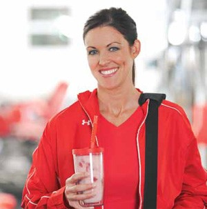 A smiling woman in red holding a strawberry-pineapple smoothie