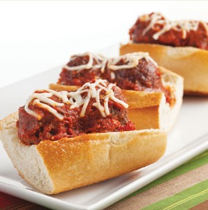 Open hoagie rolls topped with warm meatballs, spaghetti sauce and shredded mozzarella