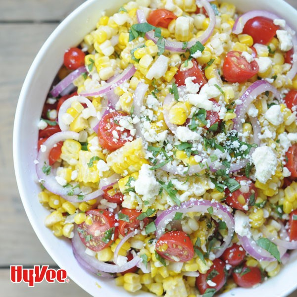 White bowl filled with kernel corn, halved cherry tomatoes, fresh basil, sliced red onions, and crumbled cheese
