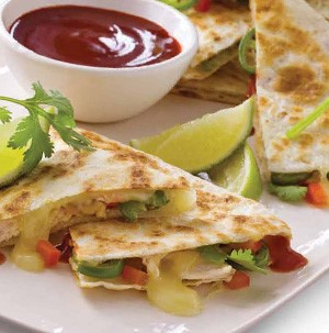 Plate of barbecue chicken quesadillas served with cilantro, lime and bowl of barbecue sauce