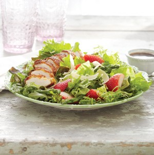 Plate of arugula salad topped with parmesan-crusted chicken, aspargus and strawberries