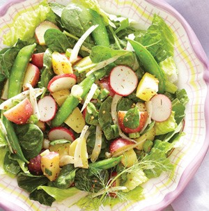 Bowl of salad mixed with new potatoes, snap peas, radishes and onion