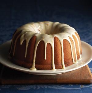 Bundt cake on white plate drizzled dripping with orange zest powdered sugar glaze