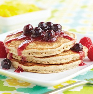 3 stacked oatmeal pancakes drenched in berry syrup with fresh berries as garnish