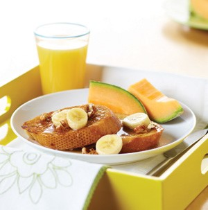 French toast topped with nuts and banana slices on a yellow serving tray with cantaloupe and orange juice