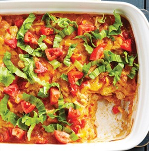 Casserole dish of cheesy chicken enchilada bake with a piece cut out