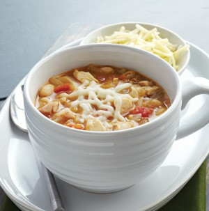 Cup of chicken bean soup, topped with melted cheese