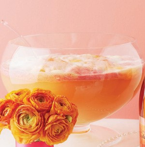 Glass bowl filled with orange and pink sherbet next to orange roses