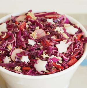Cup of coleslaw with red cabbage, red pepper strips, ramen noodles and garnished with radish-shaped stars