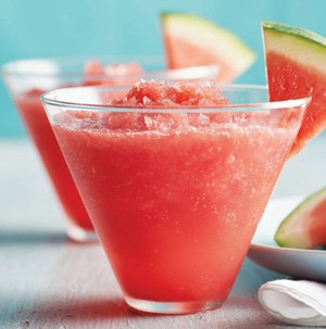 Glass filled with watermelon slush with watermelon slice on rim