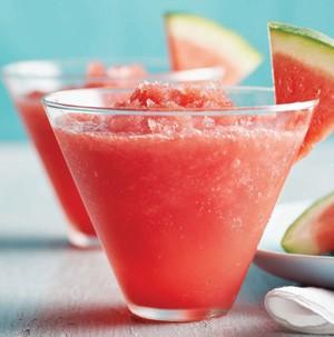 Glass filled with watermelon slush with watermelon slice on rim