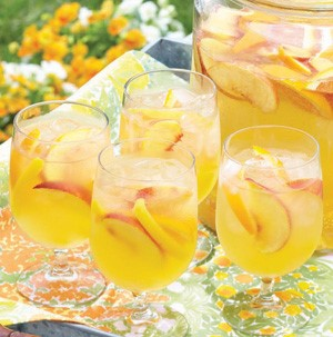 Four glasses of sangria with peach slices