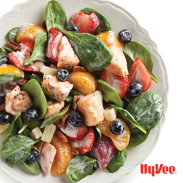 Bowl of spinach salad topped with salmon chunks, mandarin oranges and fresh strawberries and blueberries
