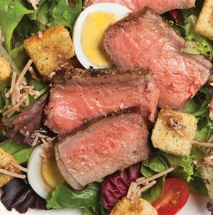 Peppered steak over plate of salad