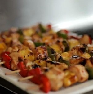 Bamboo skewered grilled chicken and bell peppers on a white plate