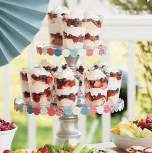 Glasses filled with layers of whipped cream and berries on a cupcake tower