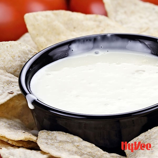 White queso dip in black bowl surrounded by flour tortilla chips