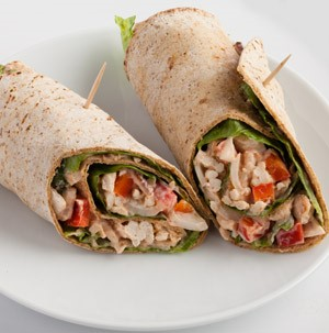 Flour tortillas wrapped around sliced turkey, red peppers, and lettuce