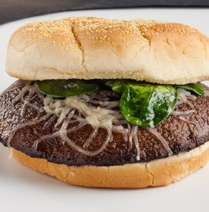 Portabella mushroom top served between a kaiser roll and garnished with melted swiss cheese and cooked spinach