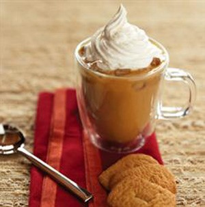 Iced coffee in a clear mug topped with whipped cream with a side of cookies on a red napkin