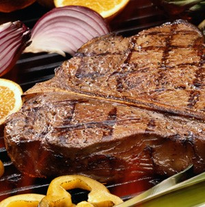 Grilled steak with red onions, sliced oranges, and yellow bell peppers