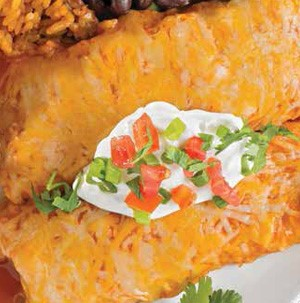 Cheesy enchiladas topped with sour cream, diced tomatoes, sliced green onions, finely diced hatch peppers, and garnished with fresh herbs
