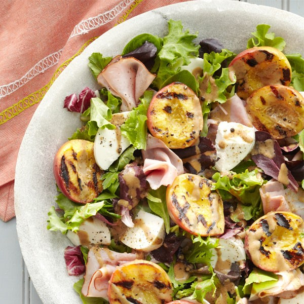 White bowl filled with fresh mozzarella cheese, grilled peach halves, sliced deli ham and mixed greens