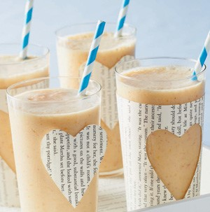 Tall glasses filled with smoothie and topped with a blue and white stripped straw and cut-out newspaper hearts
