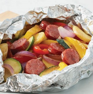 Aluminum pouch filled with sausage, sliced zucchini, red onions, bell peppers, and yellow summer squash
