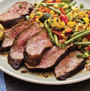 Sliced grilled steak on a white plate with grilled green beans, squash, corn kernels, and sliced green onions