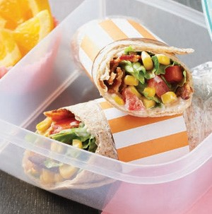 Wraps in a plastic container filled with bacon, corn, chopped tomatoes, and lettuce