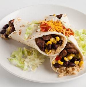 Two flour tortillas wrapped around chopped cooked beef, rice, corn, and black beans topped with salsa and shredded cheese