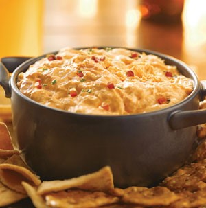 Grey Dutch oven filled with buffalo chicken dip and surrounded by chips