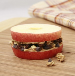 Peanut butter, granola, chocolate chips and raisins sandwiched between two apple slices