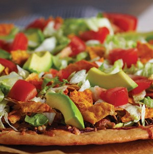 Thin cursted pizza topped with sliced avocado, diced  tomatoes, cooked ground meat, and chips